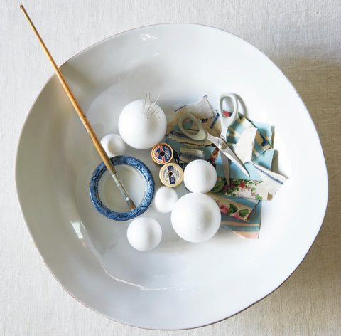 Materials needed to create a fabric Christmas bauble: styrofoam balls, elastics, fabric offcuts, paintbrush, placed in a white ceramic bowl