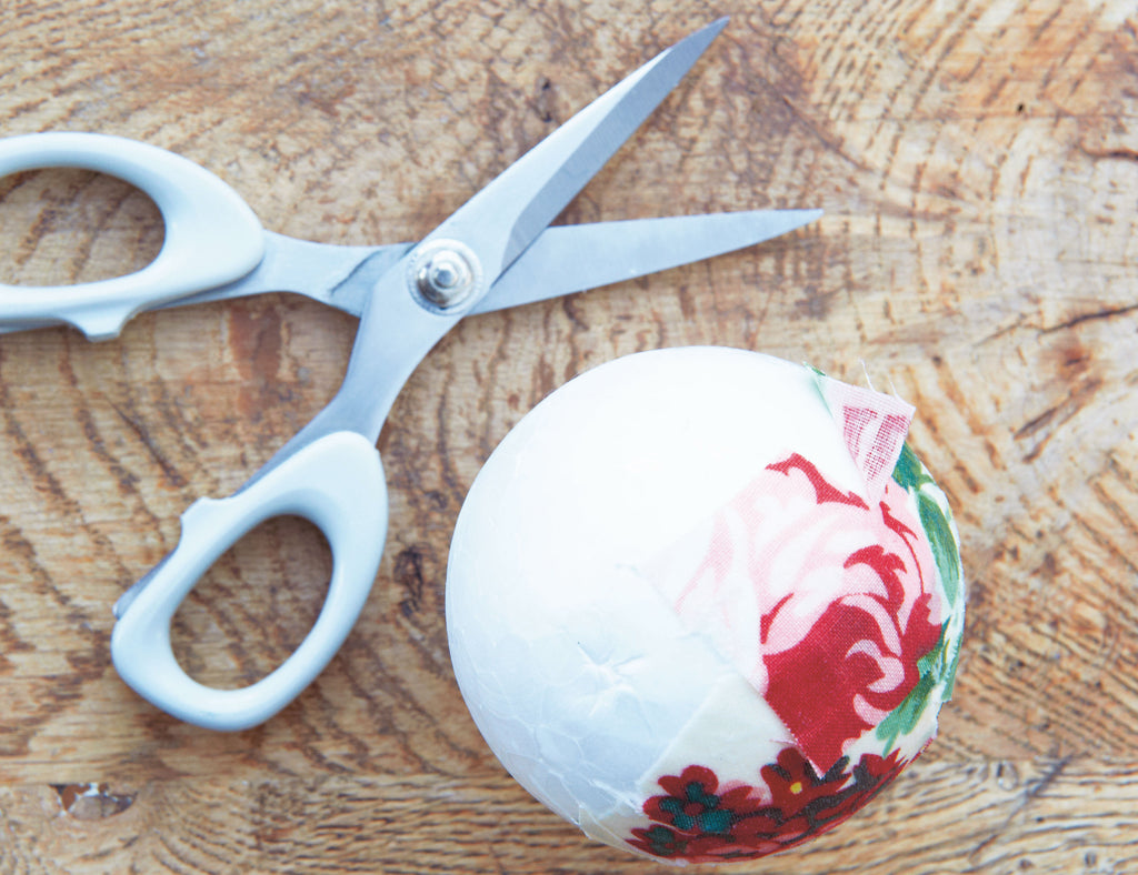 Scissors next to half covered fabric bauble