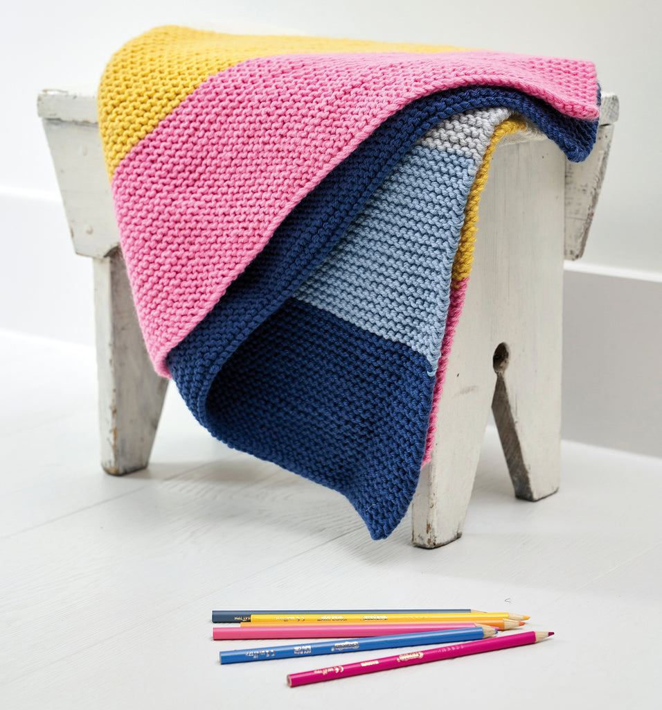 Knit striped blanket folded on a stool with matching colourful pencils in the foreground