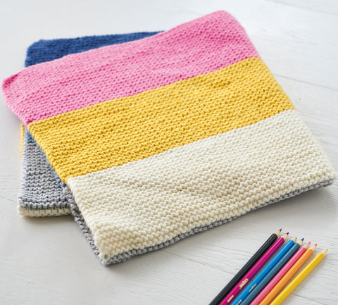 Striped knit blanket folded, next to colourful pencils that match the colours of the stripes