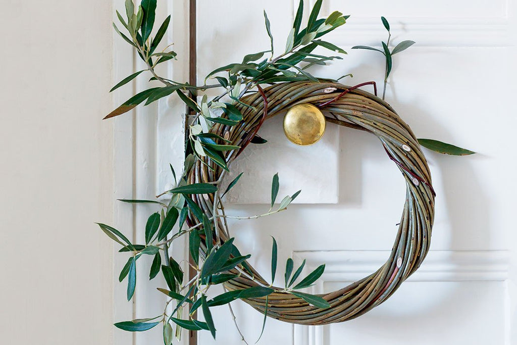 A willow wreath with holly hanging from a door