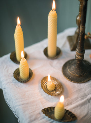 Rolled beeswax candles in candle holders on table