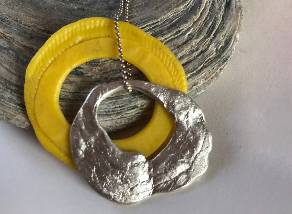 Silver pendant and yellow plastic bead on a silver chain.