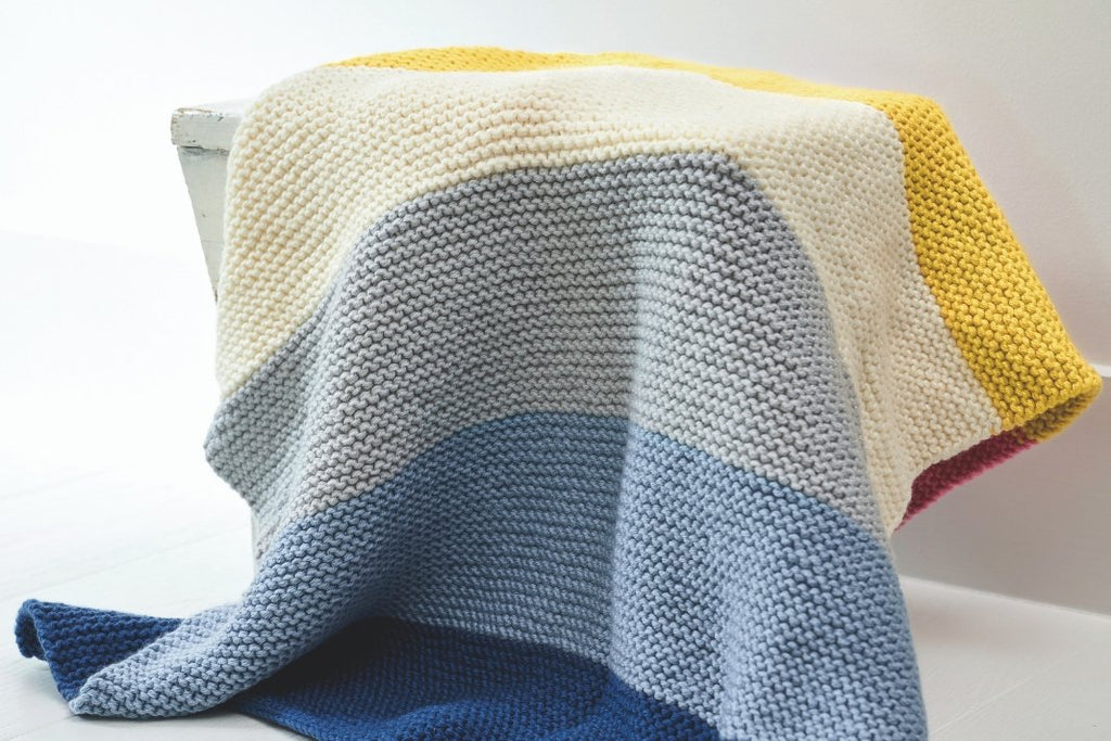 Editorial shot of knit striped blanket covering a chair