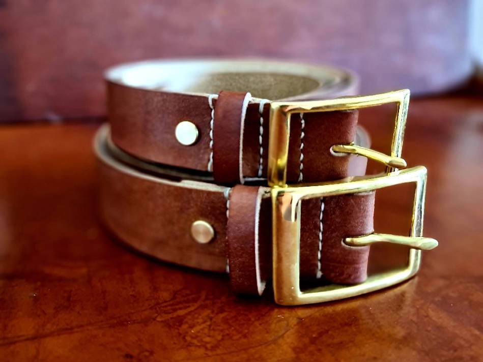 Two leather belts with gold buckle folded on top of each other