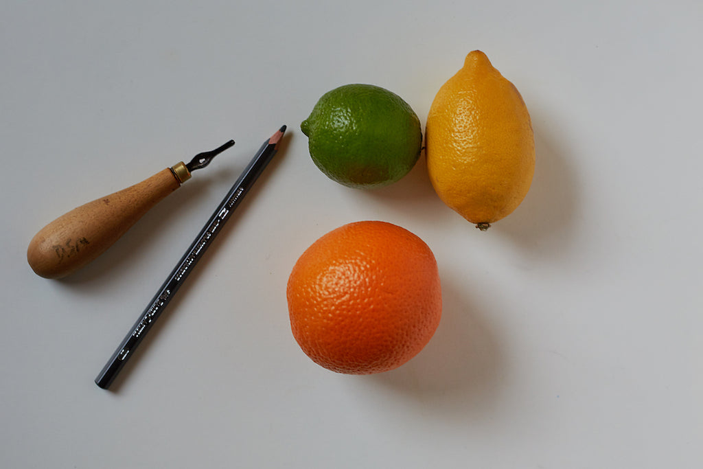 Tools you need to linocut citrus fruits: a lemon, lime and orange, linocut tool and a pencil