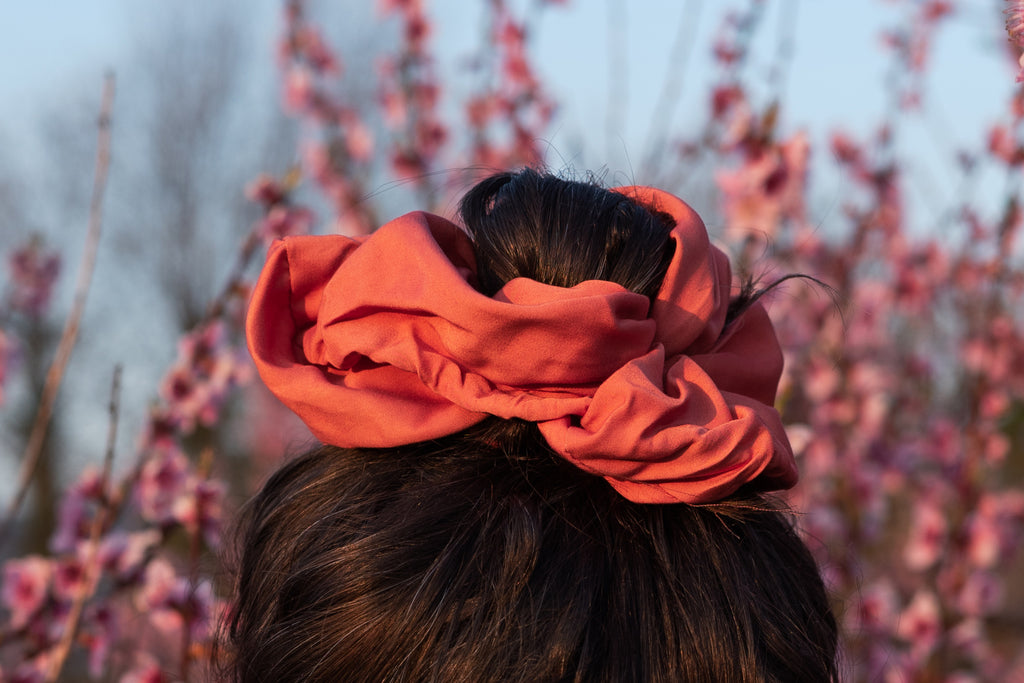Pink scrunchie on a high bun on brunette hair, with pink flowers in the background