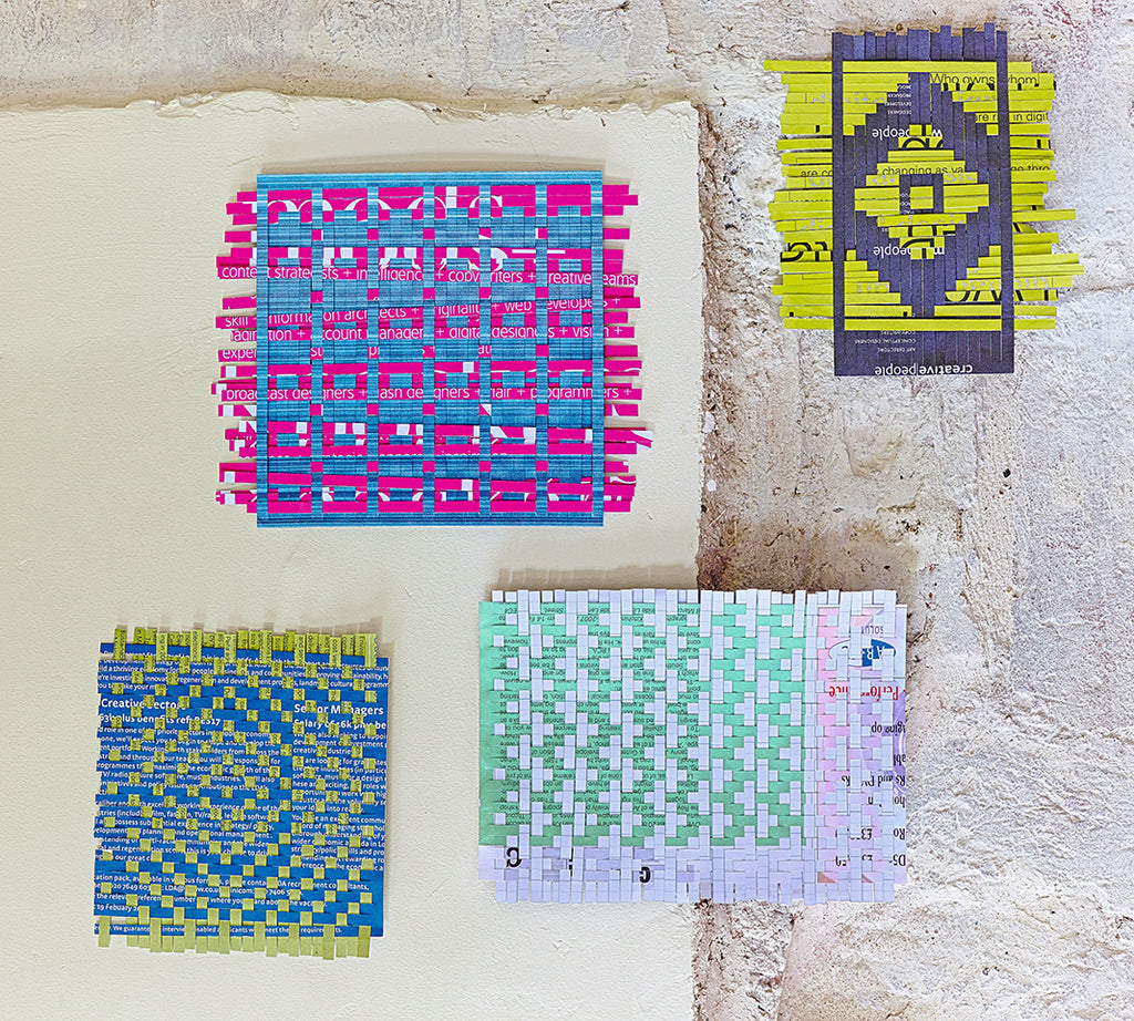 Four pieces of colourful woven paper against a concrete background