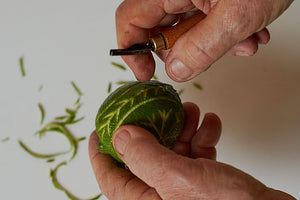 The process of lino-cutting a lime with a linocutting tool