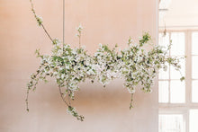Load image into Gallery viewer, A hanging floral arrangement made with spring blossoms.