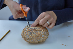 The process of making a weave basket, cutting the ends of the lapping cane.