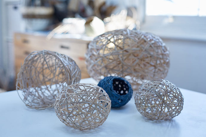 An assortment of completed random weave baskets placed on a white table, all of which are white except for a small dark blue one.