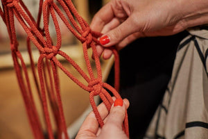 Making knots in order to create a spiral knot macrame plant hanger.