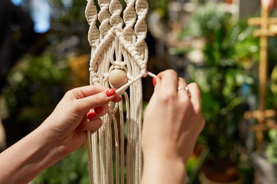 Details of Katie tying a knot in the process of making an Eye Spy macrameé wall hanging with white macramé rope.
