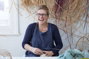 Maker Julia Clarke in her studio, surrounded by natural materials such as lapping cane and willow.