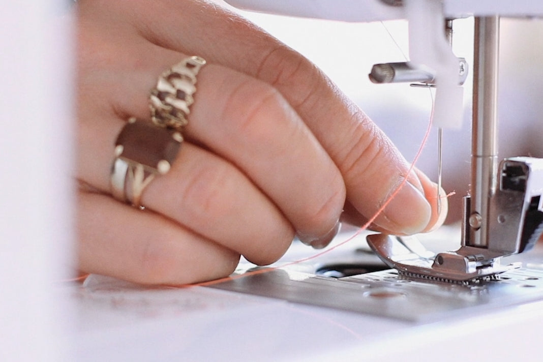 Close-up of hand feeding thread through sewing machine.