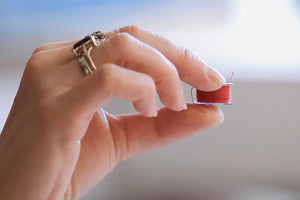 Close-up of hand holding a bobbin.