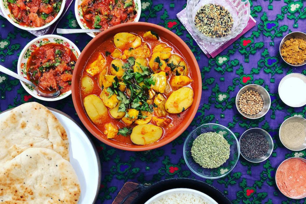 A bowl of colourful potato and cod Bangladeshi curry surrounded by other dishes, bread and spices.