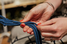 Load image into Gallery viewer, Close-up of two hands looping dark blue macramé cord.