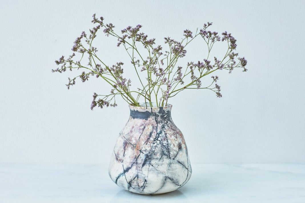 A smoke-fired ceramic vase with small purple flowers.
