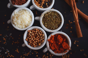 A variety of colourful Bangladeshi spices in small cups, including mustard seed and paprika, with cinnamon sticks on the side.