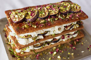 A Fig and Rose Millefeuille on a platter, a Middle Eastern pastry layered with black figs and dried rose petals, pistachios, passion fruit and honey cream.