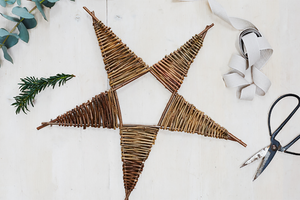 Completed willow star next to ribbon, scissors, eucalyptus branch and pin sprig.