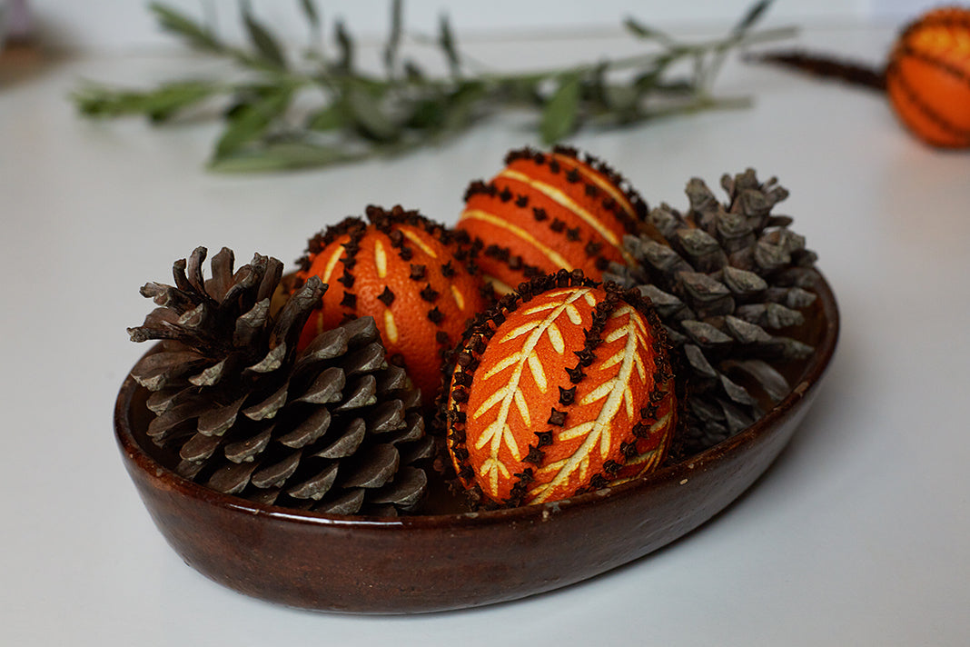 Clove-spiked oranges with intricate linocut patterns carved in, placed on a decorative plate along with some pinecones.