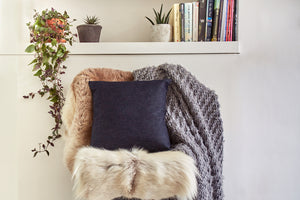 A completed denim cushion on a chair covered in soft furs, with a shelf containing books and plants above.