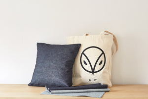 A completed denim cushion next to a Hiut Denim canvas tote bag and Hiut denium fabric.