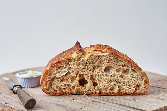 A loaf of sourdough bread sliced in half to reveal bubbly centre.