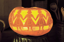 Load image into Gallery viewer, Pumpkin carved with maidens in a hand, holding hands.