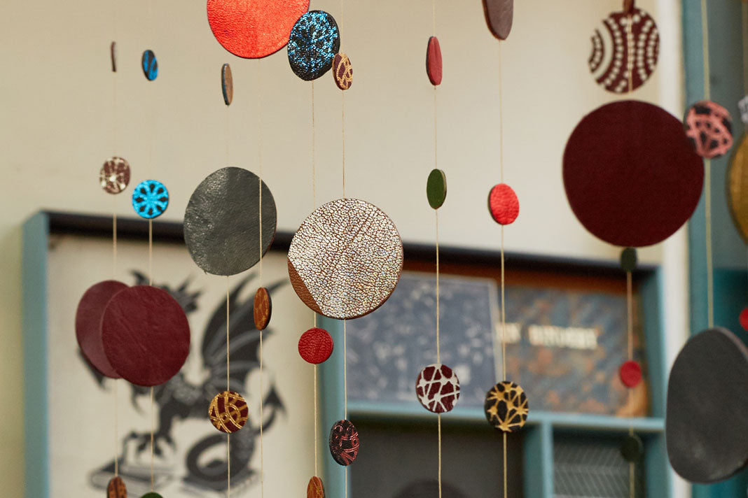Wyvern Bindery shop window, featuring decorative hangings of colourful leather circles punched out from scrap leather.