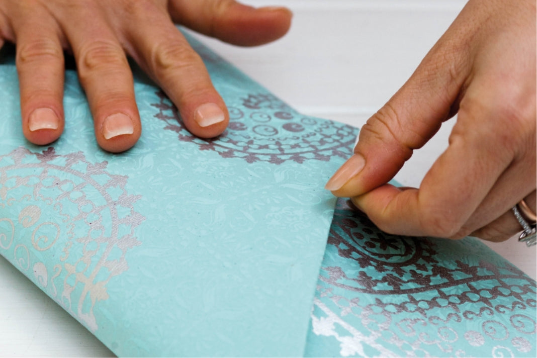 Two hands closing the near-complete gift envelope, made with light blue wrapping paper featuring a silver pattern.