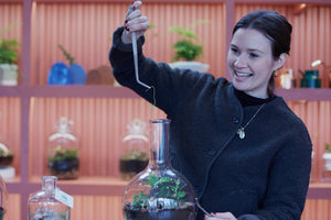 Emma Sibley of London Terrariums holding up a tweezer tool above her flask terrarium, in her shop that is filled with a variety of terrariums in the background.