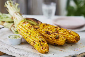 Beautifully photographed grilled corn on the cob, placed on a light grey board along with a dip.