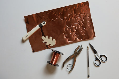All the tools you'll need to create leafy copper garlands, including a sheet of copper foil, a hole punch, a pair of scissors, copper wire, a pen and a texture wheel.