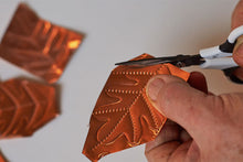 Load image into Gallery viewer, Cutting out the traced leaf from copper foil.