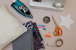 Everything you need to sew a cushion cover, including iron, fabric, thread, scissors and machine.