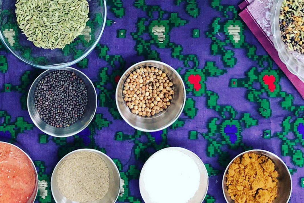 Bowls of colourful and fragrant herbs and spices on a patterned table cloth.