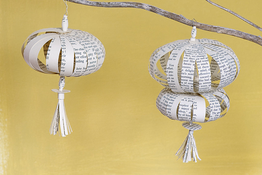 Three round tasseled decorations hanging from tree branches, made from pages of old books, against a yellow background.