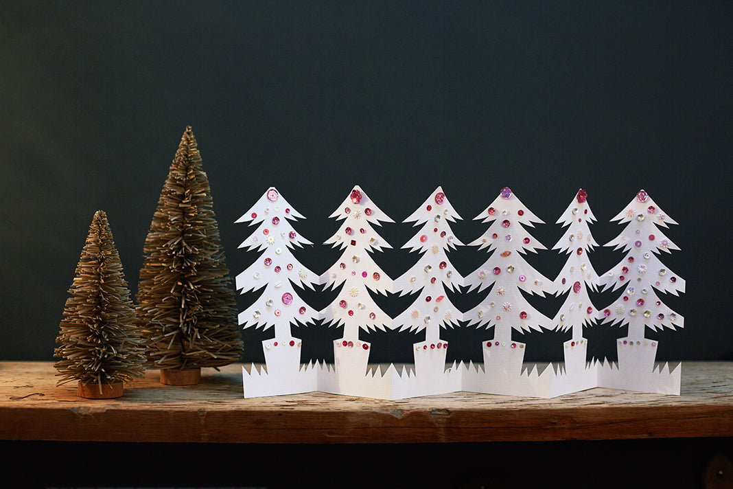 A holiday paper garland in the shape of Christmas trees, adorned in colourful jewels.