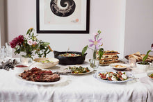 Load image into Gallery viewer, A Middle Eastern feast, with a variety of colourful dishes and ornate floral arrangements placed across a table with a white tablecloth.