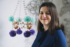 Karolina Merska standing in front of one of her Pajaki paper chandelier creations.