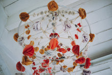 Load image into Gallery viewer, A completed pajaki paper chandelier with paper roses hanging from the ceiling.