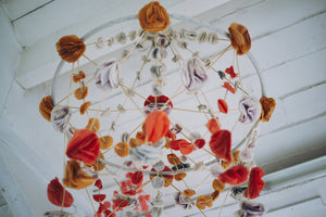A completed pajaki paper chandelier with paper roses hanging from the ceiling.