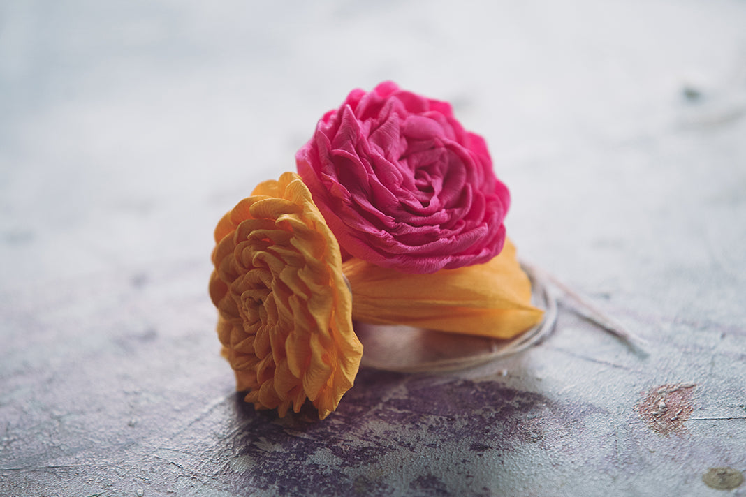 Two completed paper roses, in bright pink and orange.