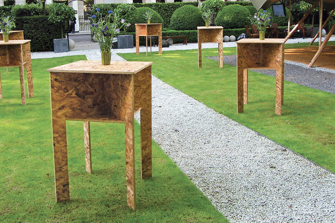 Several completed strand board tables in an outdoor green area, with a vase of fresh flowers on top of each.