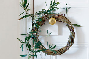 Willow wreath adorned with sprigs of holly, hanging from a gold doorknob.