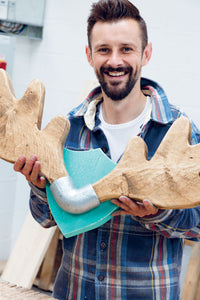 Maker Max McMurdo holding up his upcycled creation, an antler-shaped coat rack made from repurposed wood.
